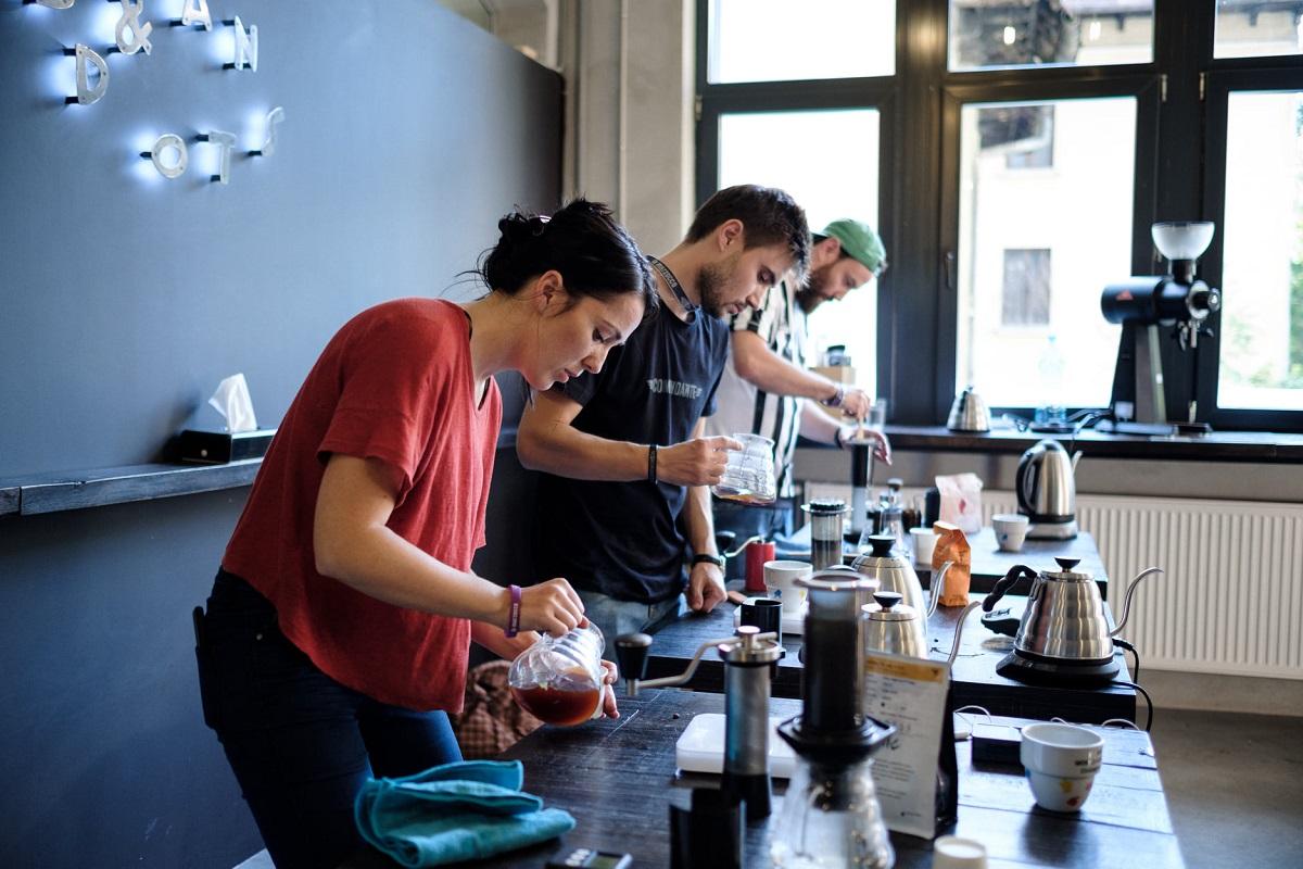 doi barbati si o femeie care prepara cafea artizanala la slow coffee festival
