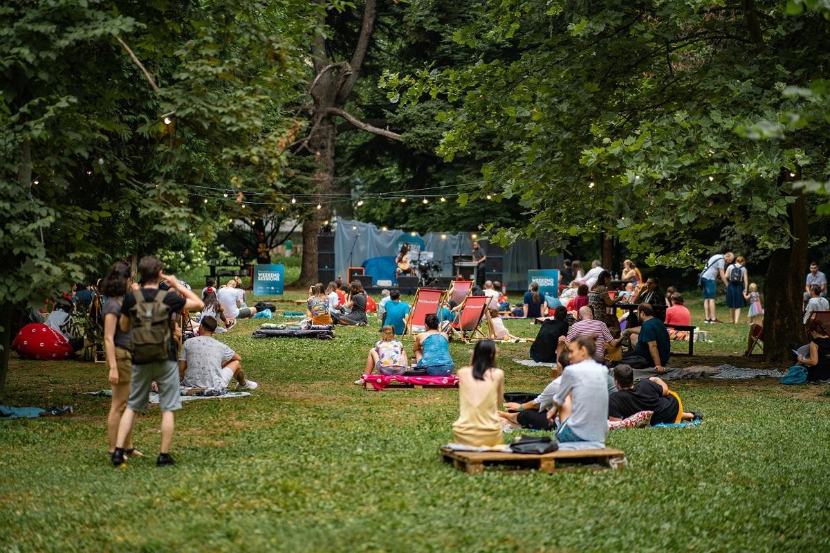 oameni asezati in iarba, pe paturi la picnic weekend sessions din Grădina Botanică, iar in fata lor o scena mica intre copacii decorati cu luminite si stegulete, recomandări de weekend București 11-12 septembrie