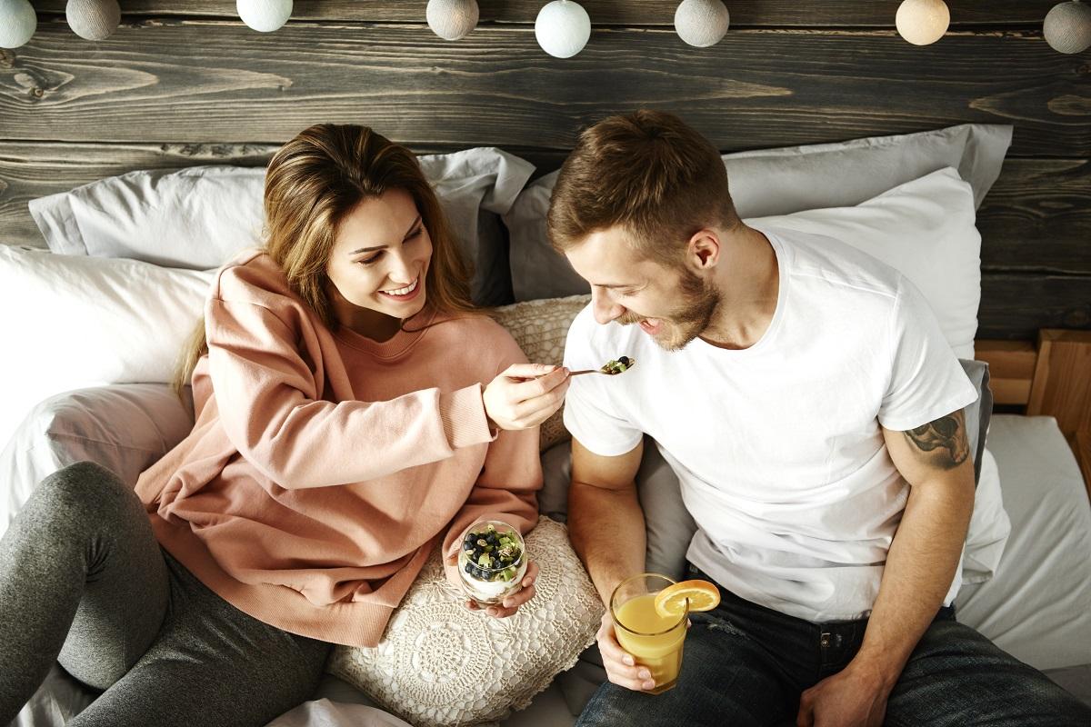 Femeie care isi imparte mâncarea cu un barbat, amandoi aflati in pat, ca idee de alimente de toamna care te ajută să dormi mai bine