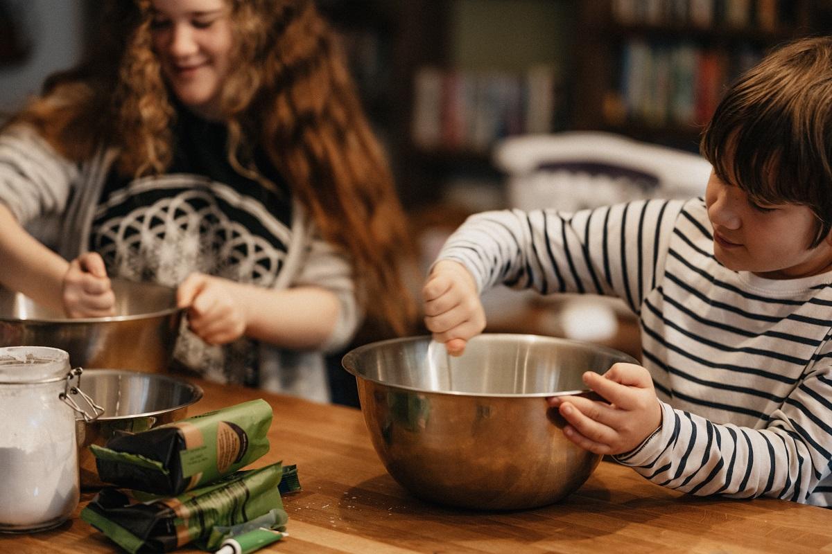 Doi copii, o fata si un baiat, amestecand cu linguri in doua boluri de inox, preparand mancare, imagine pentru cum să faci pizza cu copiii
