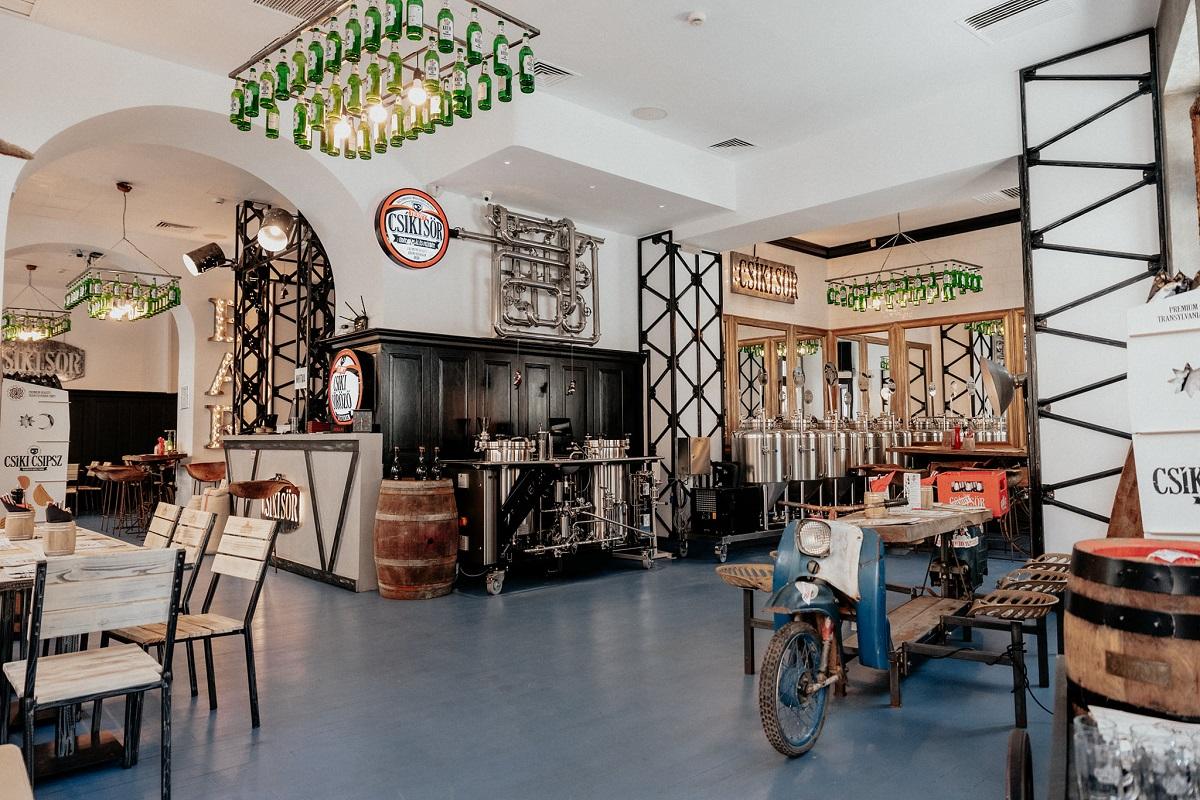 Beraria artizanala Csíki Sör din Centrul Vechi, cu butoaie de bere, mese dintre care una pe un schelet de motocicleta, cu pereti albi, o sala mare