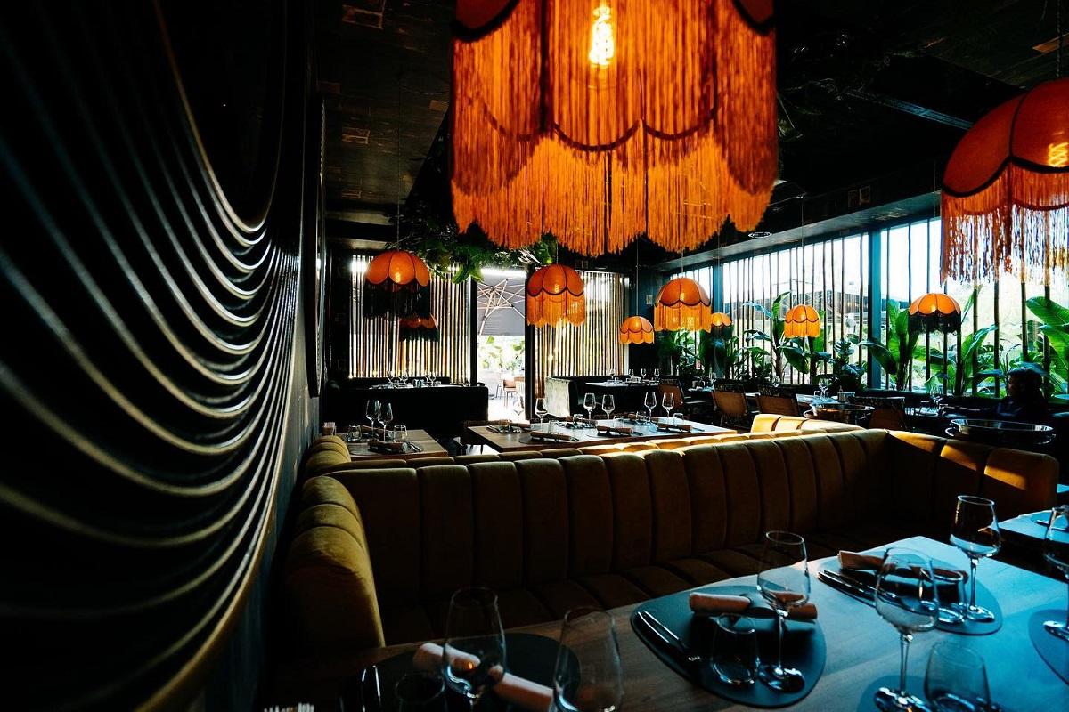 Elephant restaurant din București, iluminat difuz, cu lustre cu ciucuri, cu mese si canapele si pereti din sticlă, unul din restaurante noi București 2021
