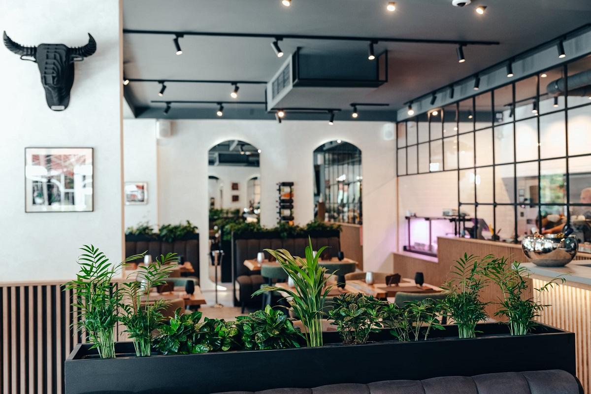 restaurant Ferma Baciu din Pipera, cu  pereti albi, un perete din oglinzi cu rame negre, mese si ghivece cu flori, unul din restaurante noi București 2021