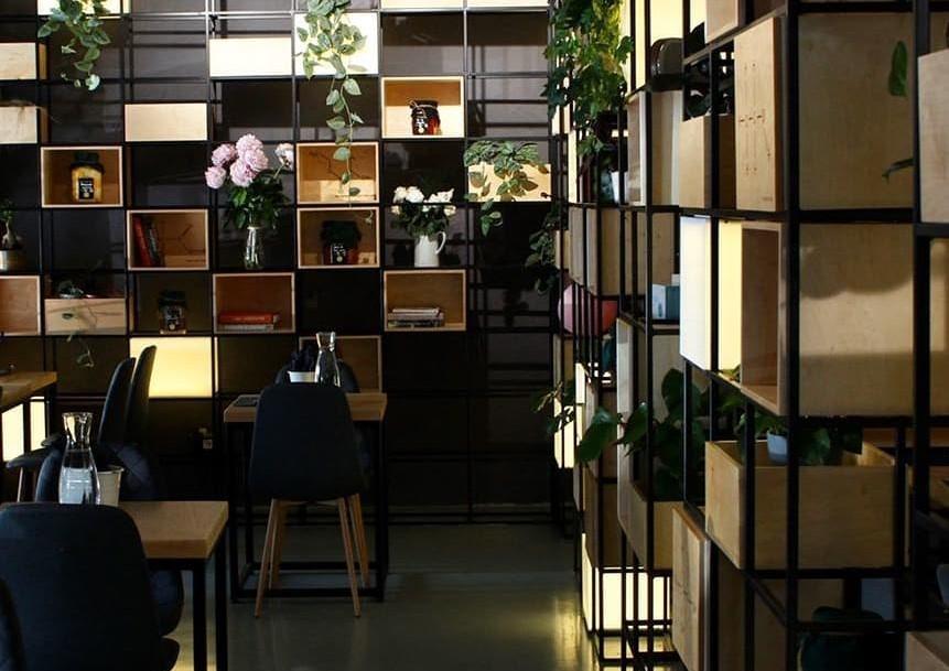 imagine din interiorul restaurantului Forager, cu pereti imbracati in rafturi cu cutii, borcane si elemente de decor, si mese, in culori inchise, unul din restaurante noi București 2021