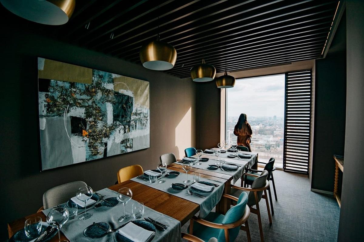 imagine dintr-un separau de la Fork Ana Tower, cu o masa lunga si o femeie in fata unui geam mare, restaurante noi București 2021