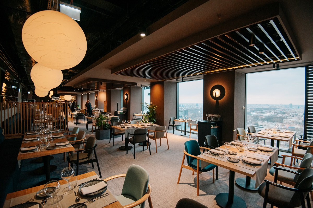 Imagine de ansamblu cu sala de mese de la restaurant Fork Ana Tower, cu ferestre mari cat peretele in dreaptam mese cu scaune capitonate si corpuri de iluminat rotunde