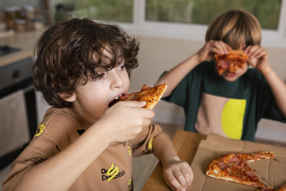 Doi copii, baieti unul musca din felie de pizza, altul ridica o felie de pizza in dreptul fetei, ca si cum se ascunde