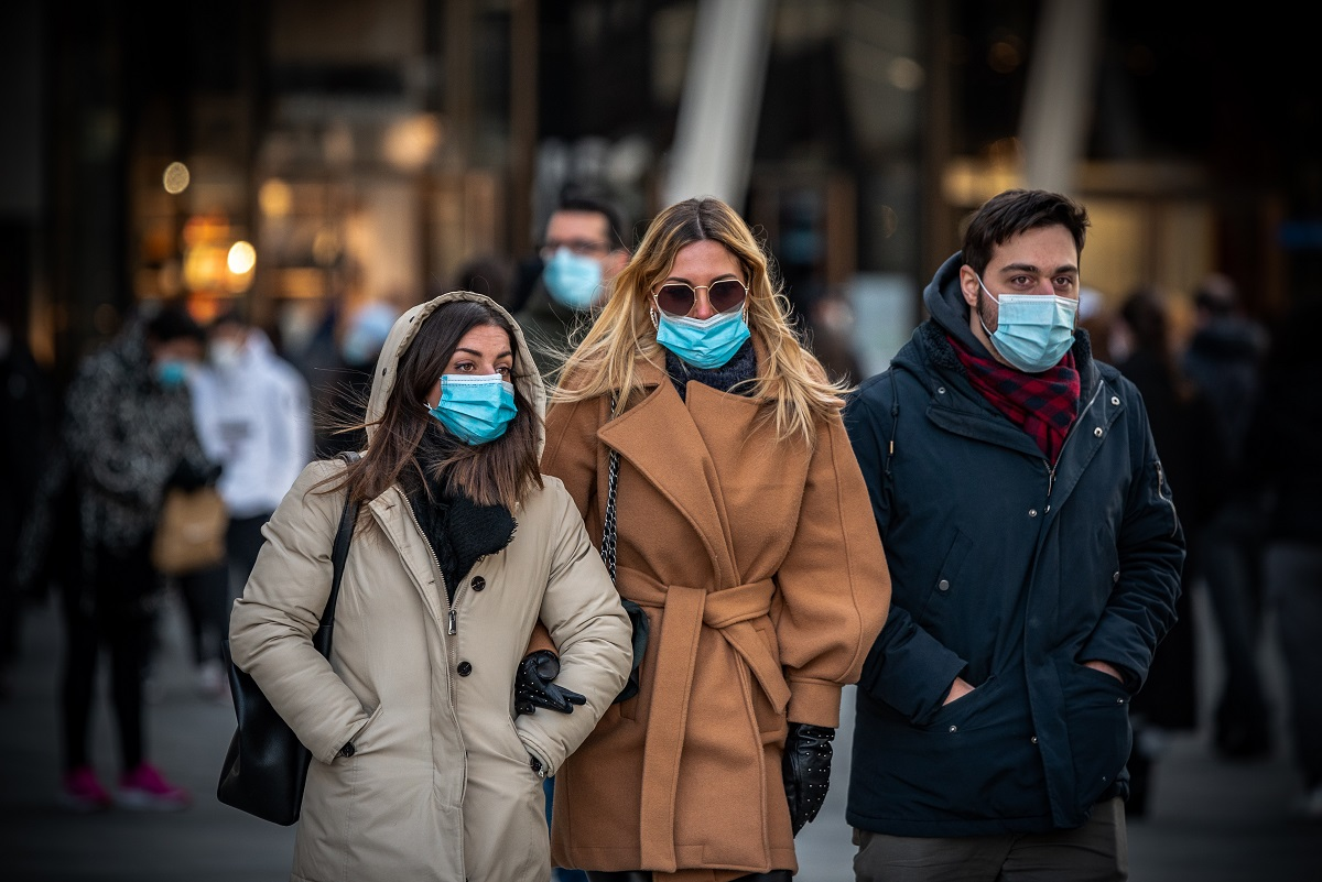grup de 2 femei si un barbat, imbracati cu haine groase, pe strada, cu masti de protectie COVID-19
