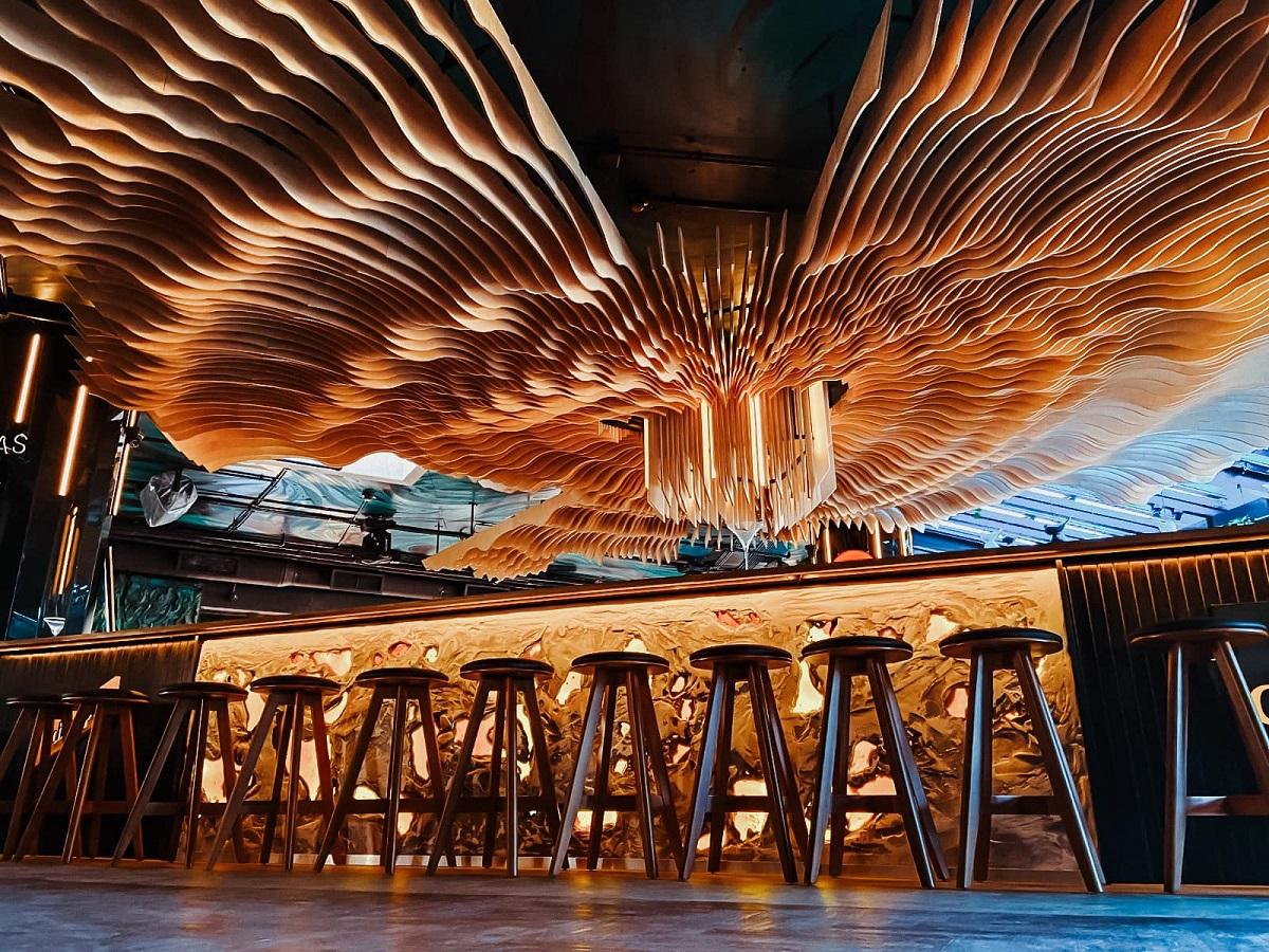 Imagine cu barul de la Naive Bucharest, cu scaune de bar insirate in fata barului luminat si un tavan plin de o sculptura din lemn asemanatoare cu un evantai