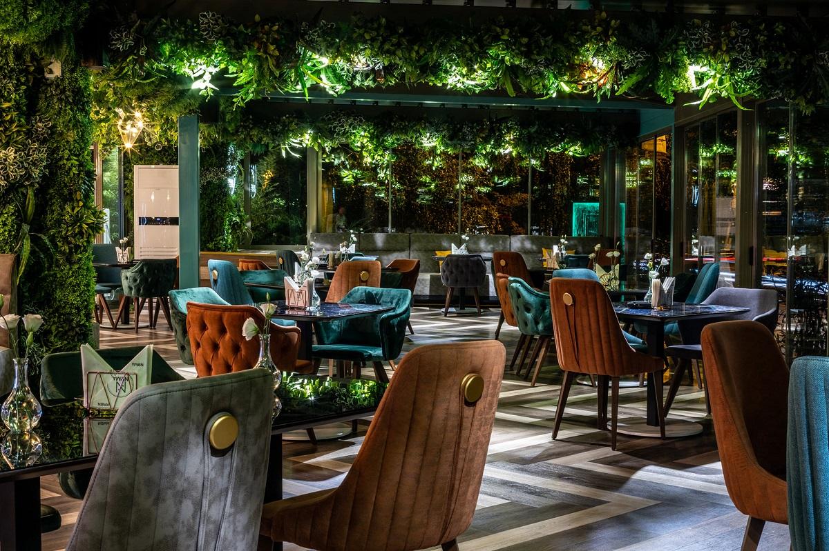 restaurant Noma Hreăstrău, cu mese rotunde si scaune tapitate in albastru si maro, cu un tavan plin de plante ornamentale