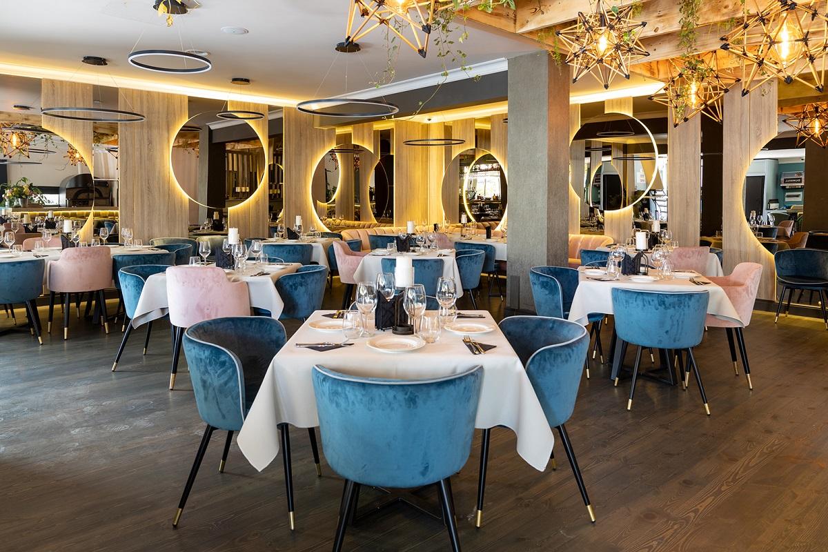 sala de mese de la Restauran O'Grada, cu mese cu fete de masa albe, scaune tapitate, turcoaz, pereti cu oglinzi mari, rotunde, luminate cu auriu