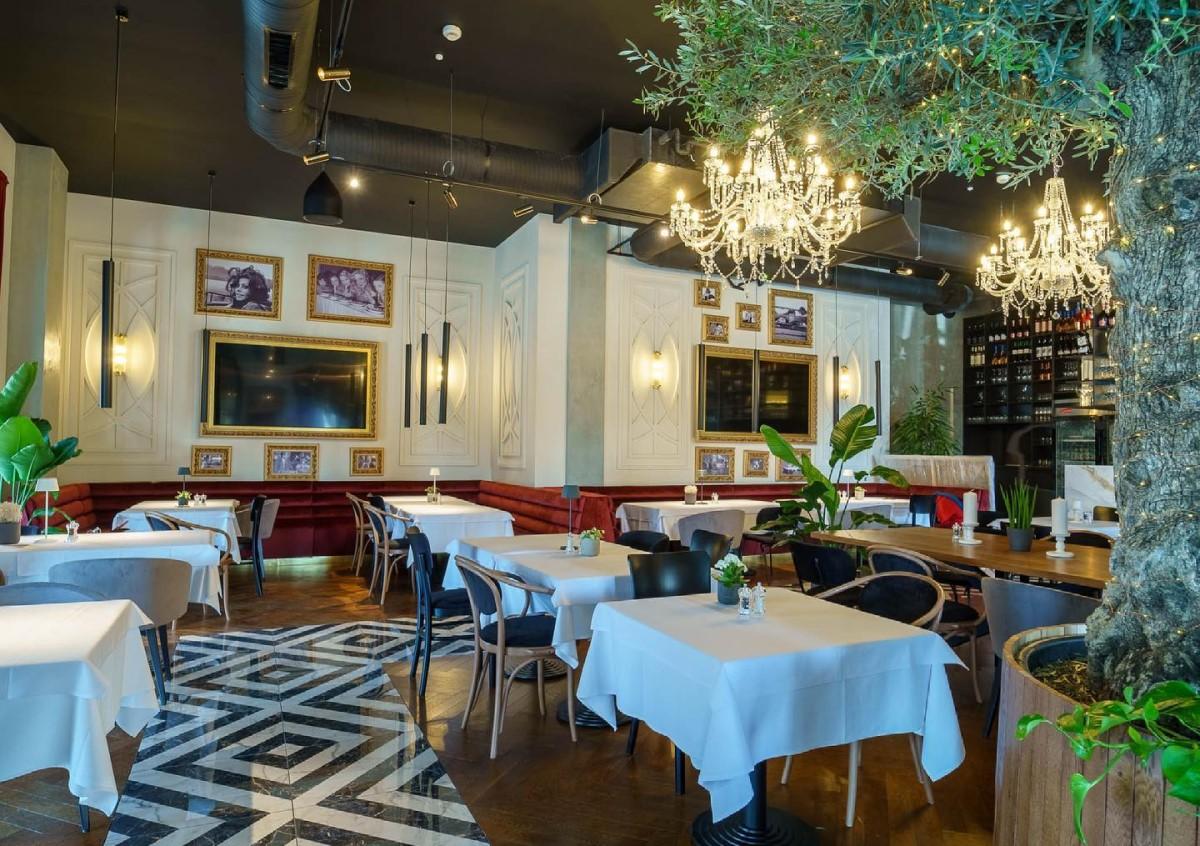 imagine din restaurantul Olivetto by Caelia, cu mese cu fete de masa albe, tablouri pe pereti, candelabre mari si ghivece cu flori inalte, unul din restaurante noi București 2021
