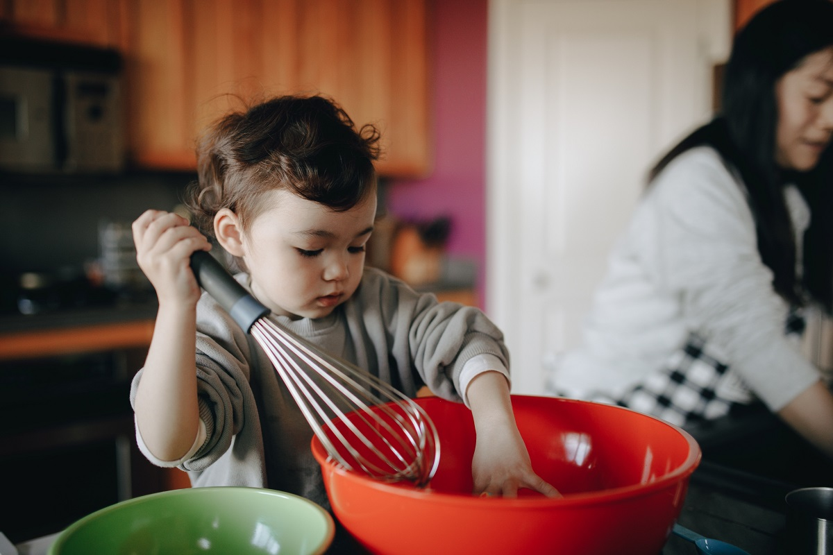 Copil de 3-4 ani, amestecand cu un tel intr-un bol de plastic rosu