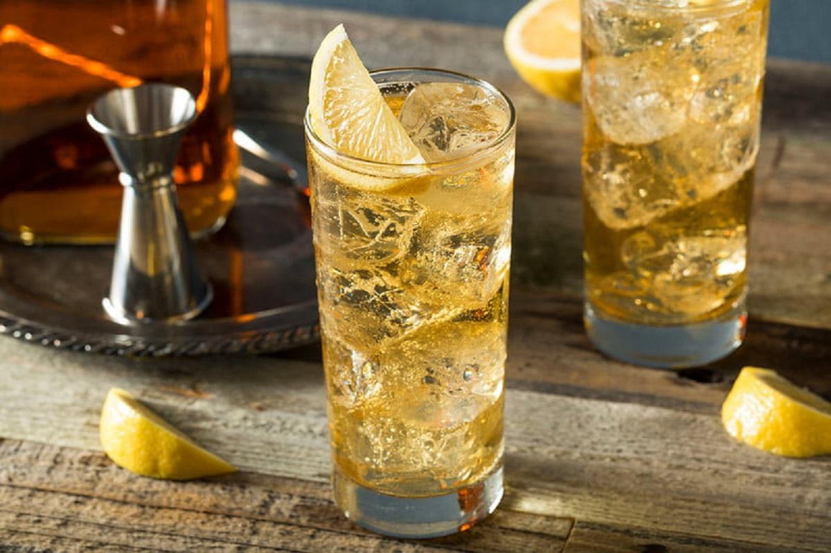 doua pahare de scotch & soda, in pahare unalte, garnisite cu lamaie